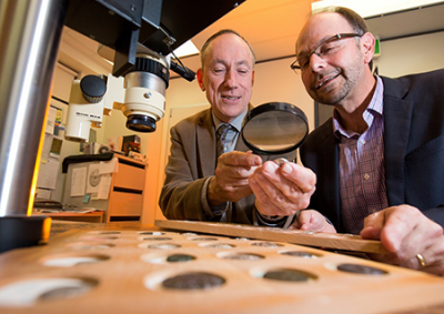 Photo of Kenneth Sheedy and Gil Davis examining ancient coins.