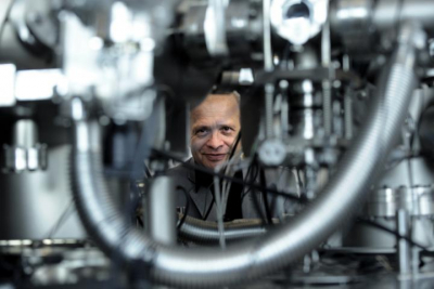 Photo of Professor Aleksander Jablonski looking through a gap in the instrument